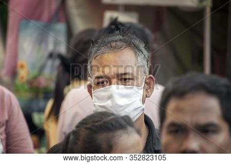 Bangkok, Thailand - February 25: Unidentified Man Wears A Face Mask As He Walks Through The Local Ma