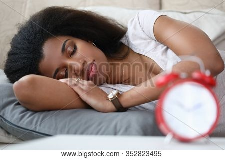 Young Woman Is Sleeping An Alarm Clock Is On Table. Beautiful Girl Takes Every Opportunity To Recove