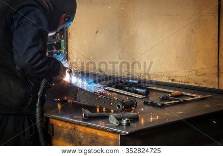 Welder erecting technical steel, Industrial steel welder in factory technical