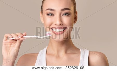 Toothcare. Smiling Girl Holding Toothbrush With Toothpaste Cleaning Teeth Over Beige Studio Backgrou
