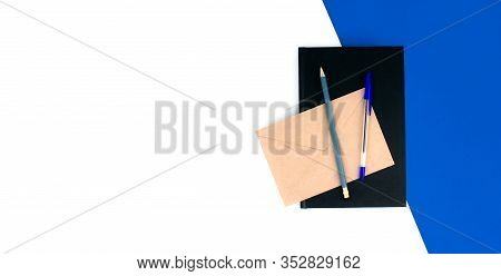 Notebook, Pen, Pencil, Envelope Flat Lay On White And Blue Background. School And Office Supplies. W