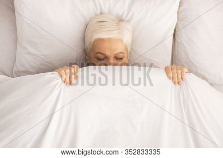 Retired Lady Lying In Bed And Playing Hide-and-seek, Hiding Under Blanket, Top View