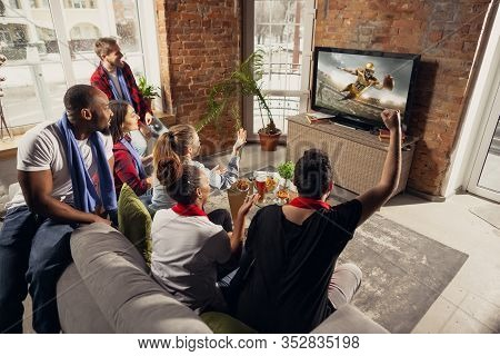 Excited Group Of People Watching American Football, Sport Match At Home. Multiethnic Group Of Emotio