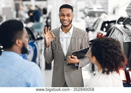Professional Car Dealer Gesturing Okay Talking With Clients Offering Great Deal Working In Auto Deal