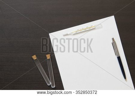 Template Of White Paper With Pen, Bottle And Thermometer On Dark Wenge Color Wooden Background. The