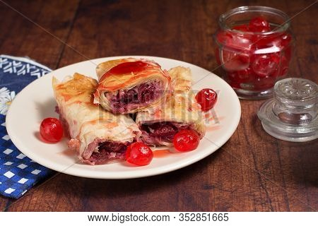 Sour Cherry Filo Pie With Syrup Poured Over It. Candied Cherries Are Placed Around Pieces Of The Pie