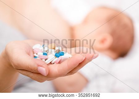 Mother holding handful of pills and tablets while breastfeeding newborn baby. Breastfeeding and medication concept