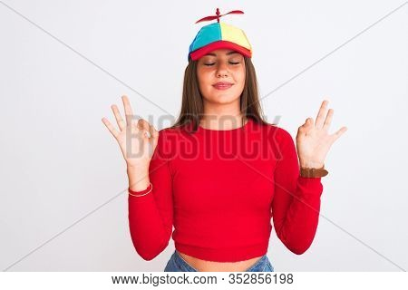 Young beautiful girl wearing fanny cap with propeller standing over isolated white background relax and smiling with eyes closed doing meditation gesture with fingers. Yoga concept.