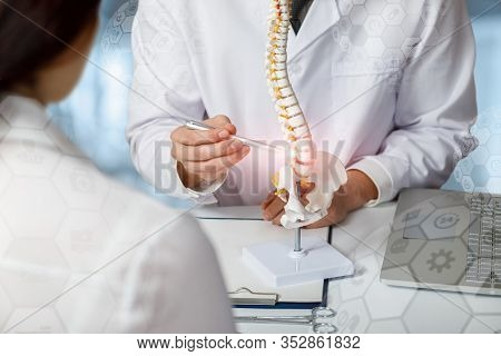 Doctor Advising Patient About Problem Areas Of The Spine On A Blurred Background.