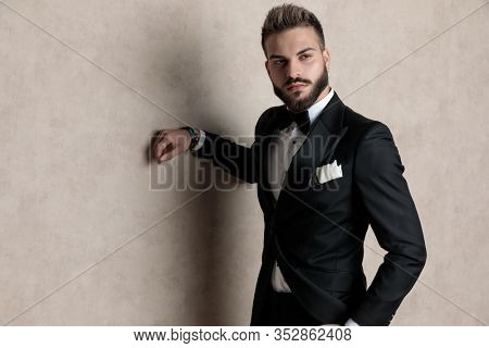 Tough groom looking away with his hand in his pocket while wearing tuxedo and standing on wallpaper studio background