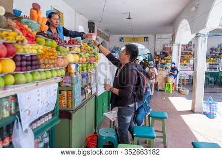 SUCRE / BOLIVIA - APRIL 10, 2018: Woman gives natural juice to the customer and looks at the camera on the local market in the city of Sucre in Bolivia