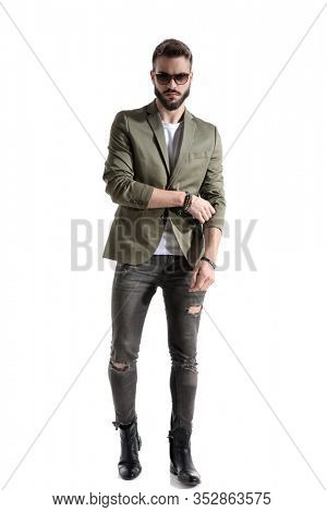 Tough model adjusting his sleeve while wearing sunglasses, stepping on white studio background