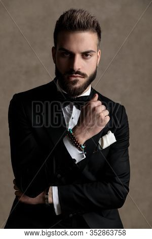Tough groom biting his lip and holding his fist clenched while wearing tuxedo and sitting on a stool on wallpaper studio background