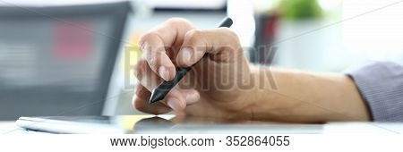 Focus On Male Hand Holding Stylos And Pointing On Tablet Screen. Man Designer Creating New Biz Proje