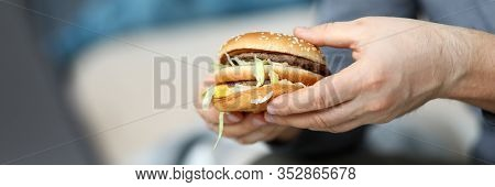 Focus On Male Hands Holding Big Unhealthy Cheeseburger Full Of Quick Carbohydrates And Harmful Chole
