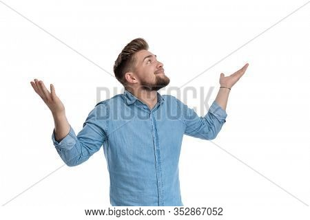 Young casual man gesturing that he does not know while wearing shirt, standing on white studio background