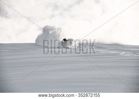 Male On A Snowboard Glides On A Snowy Mountain Slope