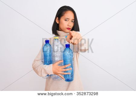 Young beautiful chinese woman recycling plastic bottles over isolated white background pointing with finger to the camera and to you, hand sign, positive and confident gesture from the front