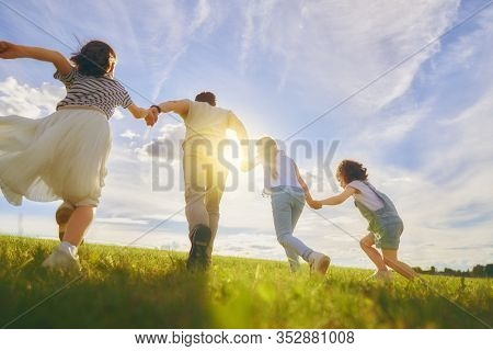 Happy family on summer walk! Father and daughters walking in the Park and enjoying the beautiful autumn nature.