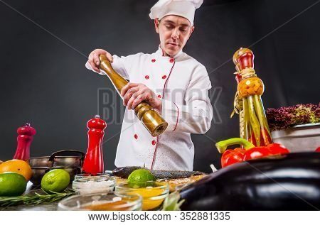Chef Adding Peppers Mix To Fish Using Big Pepper Mill