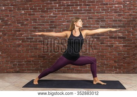 Side View Portrait Of Beautiful Young Woman Wearing Black Top And Purple Leggings Working Out Agains