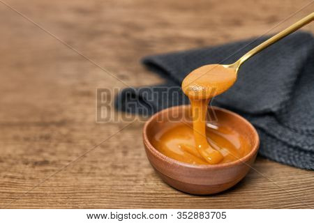 Manuka honey dipper dipping in raw organic liquid from Manuka flowers in New Zealand .Bees harvesting exclusively from this healthy antibacterial antifungal property flower.