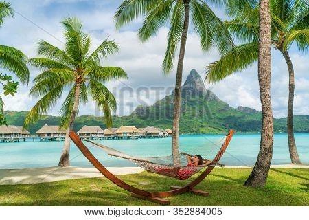 Luxury vacation honeymoon resort tourist woman in hammock by overwater bungalow hotel Bora Bora, Tahiti, French Polynesia. Exotic summer travel. relaxation getaway.