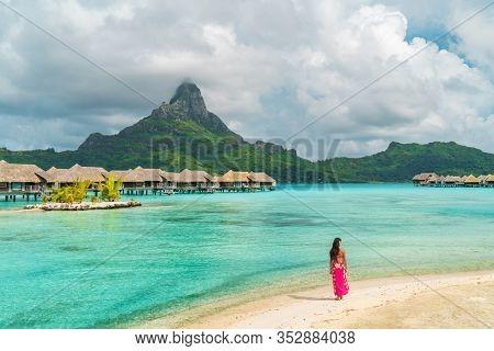 Bora Bora luxury resort honeymoon vacation destination in Tahiti, French Polynesia. Woman walking on idyllic beach landscape.