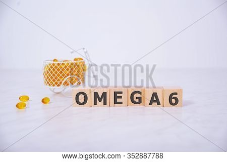 Pills Drugs Omega 3 6 9 Omega Fish Oil. Word On Wooden Cube.