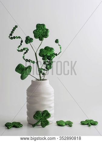 St. Patrick's Day Green Swirls, Four Leaf Clovers And A Hat In A White Vase With More Glittery Green