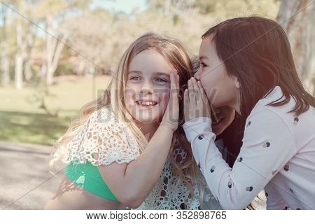 Mixed Ethnic Young Little Girls Playing Kids Chinese Whispering In The Park, Best Friends And Positi