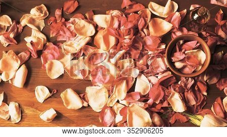Aroma Oil Bottle And Clay Bowl Among Roses Petals On Wooden Surface, Toned Warm, Top View, Selected