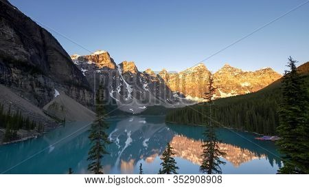 Sunrise Shot Of Moraine Lake At Pine Trees In Canada