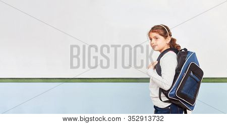 Girl stands with schoolbags as a freshmen in front of a white board in elementary school