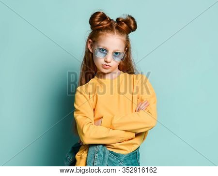 Cool Red-haired Teenager Girl Fashion Trendsetter In Smoked Blue Glasses And Yellow Sweatshirt Is Po