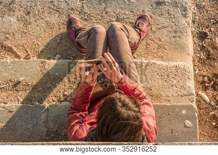 Top View Of A Brunette Woman Sitting On The Stairs Of A Beach, Shooting A Photogragh Or Video With H