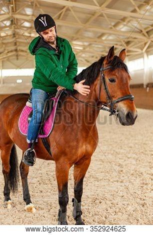 Man Jockey Sitting On Horse, Horseback Training On Manege, Lesson For Jockey In Equestrian School Or