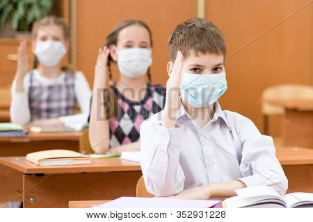 School Kids With Protection Masks Against Flu Virus At Lesson In Class