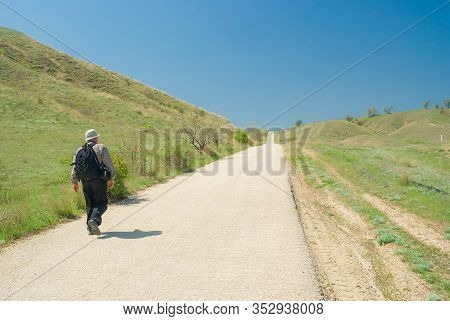 Lonely Hiker Walking On An Empty Asphalt Road At Spring Season, Crimean Peninsula