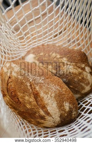 Different Buns Of Fresh Bread In Wicker String Bag. Freshly Baked Wheat Bread, Still Life With Bread