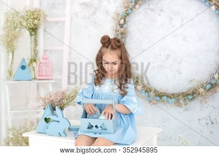 Little Girl Sitting On A Table In A Blue Dress Holding A Basket With Easter Eggs. Easter Interior. S