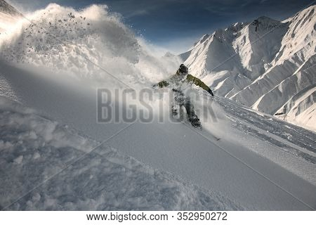 Freerider Slipping Down The Mountain Through The Snow