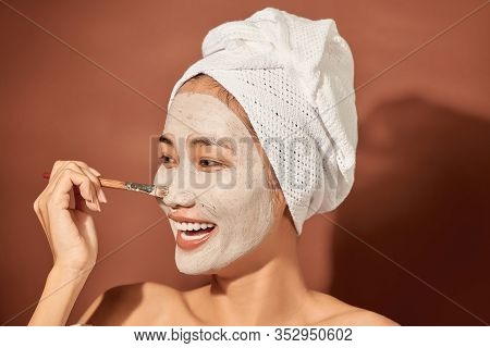 Young Beautiful Woman With Clay Mask On Her Face. Salon Skin Care, Natural Cream Of Algae.