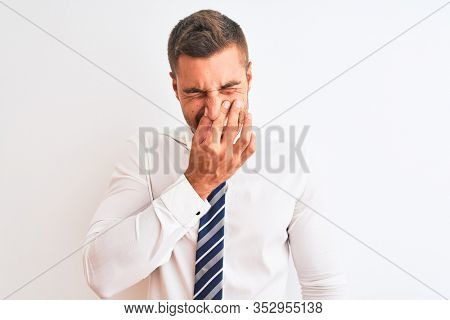 Young handsome elegant business man over isolated background smelling something stinky and disgusting, intolerable smell, holding breath with fingers on nose. Bad smells concept.