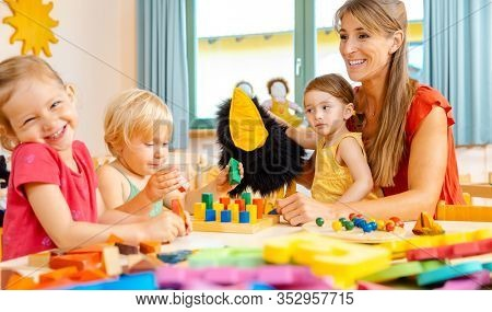 Kindergartener woman with children playing a game