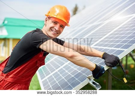 Installer Inspecting Solar Panels On A Plot Near The House. A Man Looking To The Camera, Wearing An