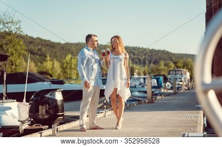 Elegant couple walking between the boats on a river port