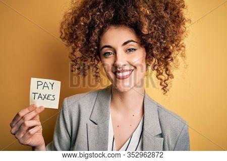 Young business woman with curly hair holding pay taxes to goverment reminder over yellow background with a happy face standing and smiling with a confident smile showing teeth