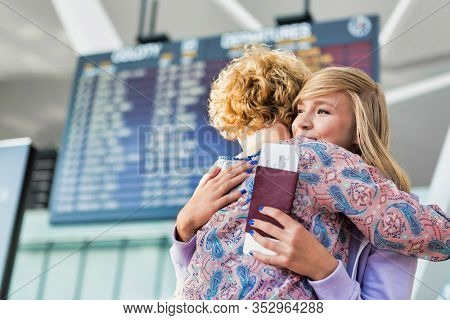 Young teenage girl reuniting with her mother in airport