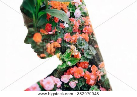 Portrait of pretty woman with long hair and summer flowers background (double exposure, tilt-shift lens blur)